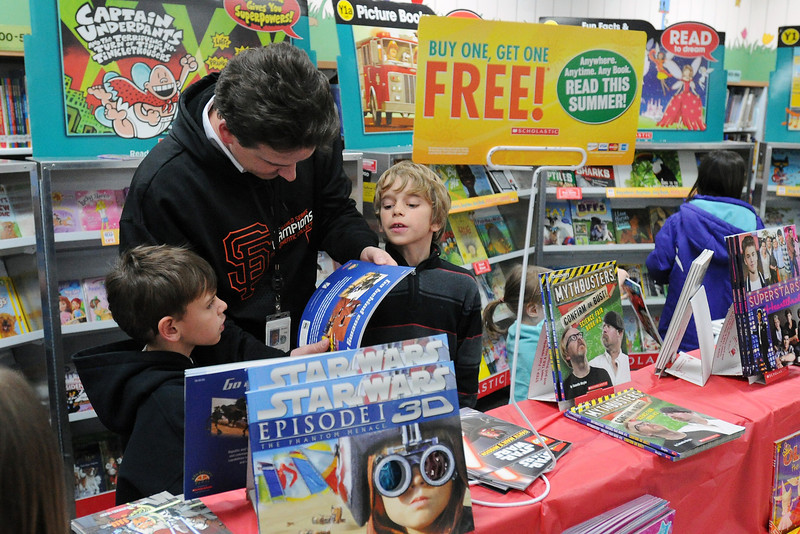 Namaqua Elementary School first-grader James Aust, 7, left, his father Jon Aust and brother Nick Aust, 10, look at books on sale during a Book Fair in the school's library Tuesday as part of the Family Literacy Night event.
