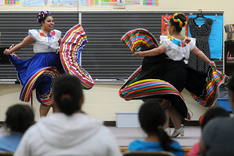 Colorado Mestizo Dancers members Tashina Lucero, left, and Carra Garcia perform a dance called La Negra during a potluck event Friday, April 26, 2013 at Winona Elementary School.