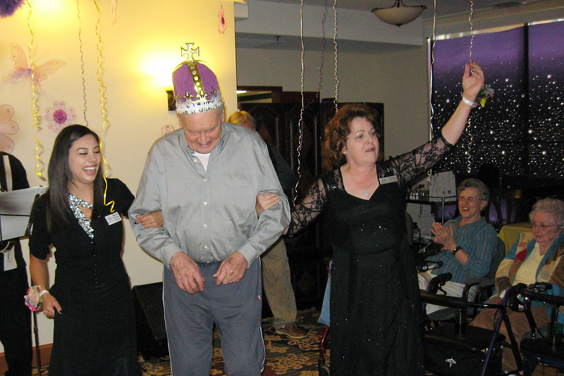 The Hillcrest of Loveland staff members Jamie Felton, left, and Donna Hamernik lead Jim Garrison, a resident there, to the dance floor after he was crowned king for the second annual ÒSeniorÓ Prom on Friday.