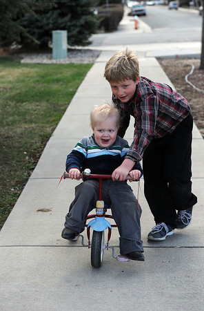 Caleb Green, 7, helps his little brother, Joel Green, 4, ride his tricycle in front of their Loveland home on Thursday, April 11, 2013. Jole's family considers him to be a miracle becaue he has overcome 7 cancerous tumors and is still going through treatment for another.