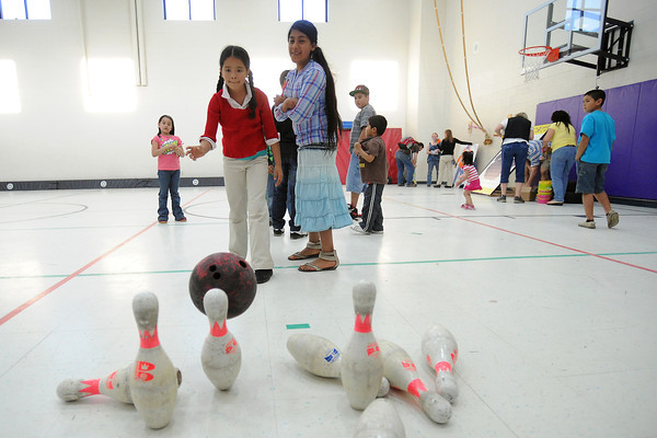 Emilly Gonzalez, front left, bowls down some pins while Alondra Samaniego looks on while the Winona Elementary students play some games together during a potluck event Friday, April 26, 2013 at the school.
