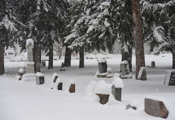 Snow covers headstones at the Loveland Burial Park Wednesday.
