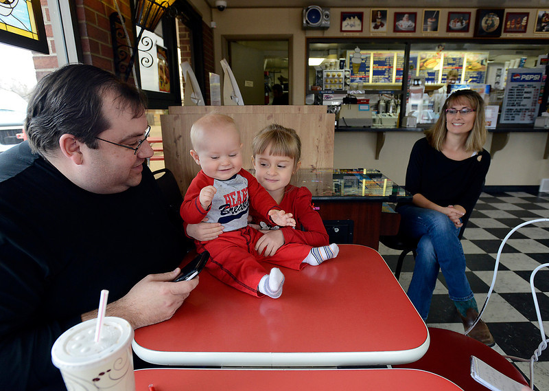 Chris Steffen, left, hangs out with his lunch buddies, William Bradford, 8 months, and Bella Bradford, 5, as their mom Christine Bradford, right, chats with Steffen while he waits for his order at Dairy Delight in west Loveland on Tuedsay, April 2, 2013. Tuesday was opening day for the ice cream shop and family diner for the season and Steffen was sure to the the first customer of the season like he has been for many years. Chrisine Bradford's parents have owned and run the business for 35 years so she grew up there and still works there.