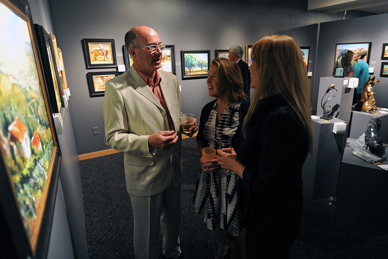 Denver resident Anthony Grant, left, and Lindasue Smollen of Boulder talk with Denver-based artist Anita Mosher about her impressionistic oil paintings during the Colorado Governor's International Art Show and Sale opening night gala on Saturday, April 27, 2013 at the Loveland Museum/Gallery.
