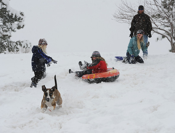 The Downing family had fun in the snow at North Lake Park on Wednesday. From left are, Zion, 5, Storm, 7, Julie and Jason. Huckle, a 1 year-old Catahoula runs down the hill.