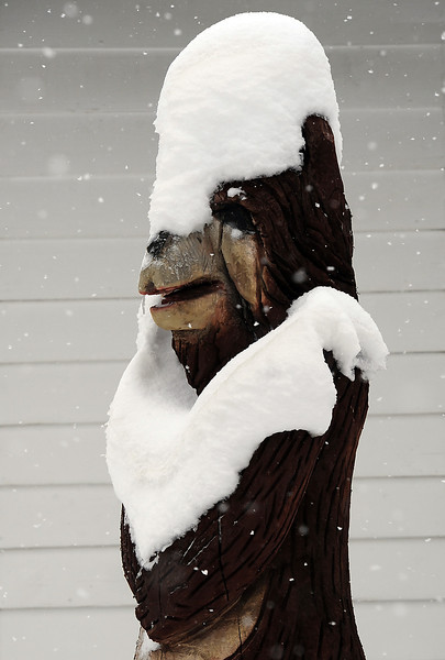A chainsaw sculpture of a bear is covered in snow Wednesday in downtown Loveland.