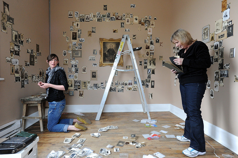 "Megan Tracy, left, currator of the ""Collections & Memories"" exhibit, and Diane Littlefield, right, collector of historical photos, hang photos from her collection in a room at the Feed and Grain on Monday, April 1, 2013."