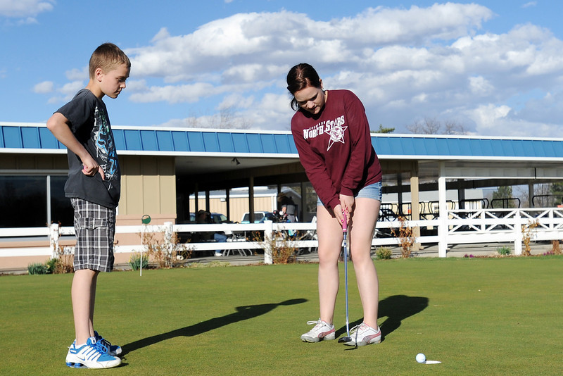 Twelve-year-old Jayden McLaughlin, left, looks on while his sister Aryn McLaughlin, 15, sinks a putt while the two practice together Friday, April 5, 2013 on the putting green at The Olde Course at Loveland.
