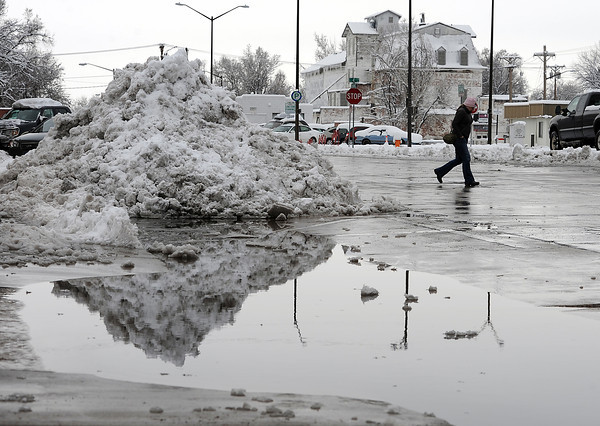 A huge pile of snow is reflected in a puddle of melted snow as Heidi Kerr-Schlaefer crosses the 400 block of Railroad Avenue on her way back to work after having lunch downtown in Loveland on Tuesday, April 16, 2013.