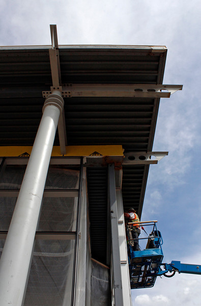 A construction worker helps install a new door Monday at the future site of Mercedes-Benz of Loveland, located in the Motorplex at Centerra in Loveland, Colo. The building is being renovated to use aesthetic features used in other Mercedes-Benz dealerships, including the futuristic pillars shown on the building's west-facing storefront.