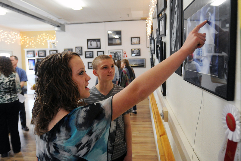 "Loveland High School sophomore Cosette Klingler, 16, left, talks with Berthoud High School sophomore Taylor Doman, 16, about her painting ""Untitled Self Portrait"" during the 2nd Congressional District Art Show on Saturday, April 20, 2013 at the Wildfire Community Arts Center in Berthoud."