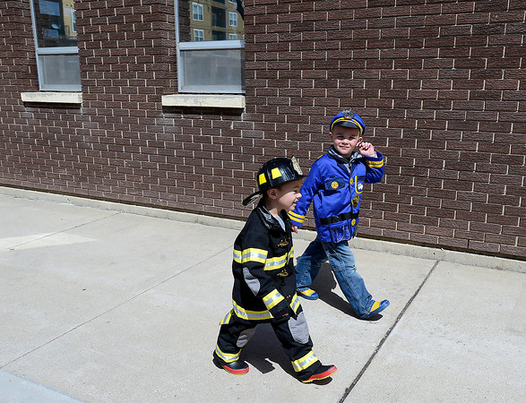 Dressed as a police officer and a Loveland Fire Rescue Authority firefighter, Rylan Adent, 3, left, and Jack Sansone, 4, walk near the fire station during Children's Day in Loveland on Wednesday, April 24, 2013.