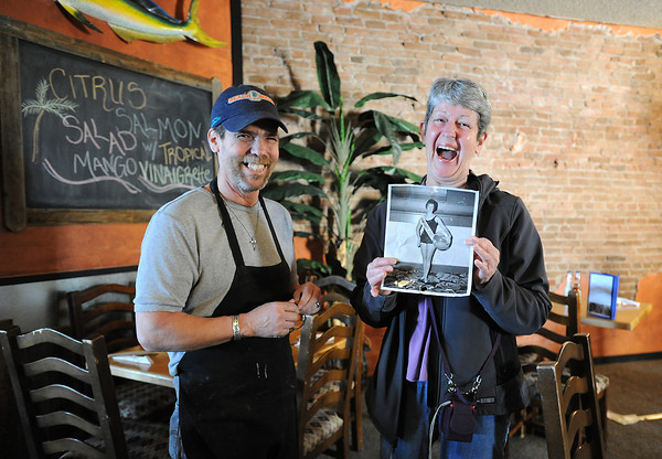 "Kay Hester Plitt, left, and Mike Severance, co-owner of the Cactus Grille in downtown Loveland, joke about what she calls the ""hysterically historical picture."" Behind them is the wall where Severance found the photo under two layers of paneling while he was remodeling the space. When two met Thursday, April 18, 2013, he gave her the photo, which shows when she was a teen as a contestant in a Miss Loveland-type contest."
