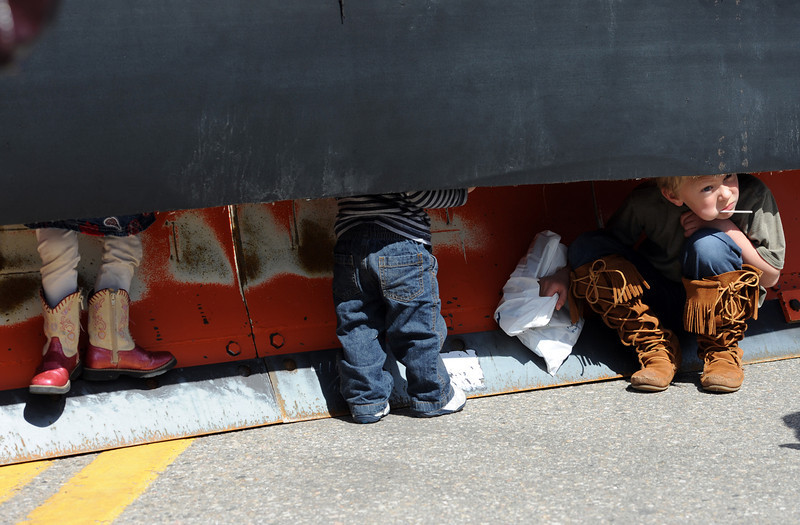 Jack Gustafson, 9, far right, peeks out from underneath a snow plow blade as Haleigh Malone, 3, left, and Nathan Malone, 1, center, stand under the blade during Children's Day in Loveland on Wednesday, April 24, 2013.