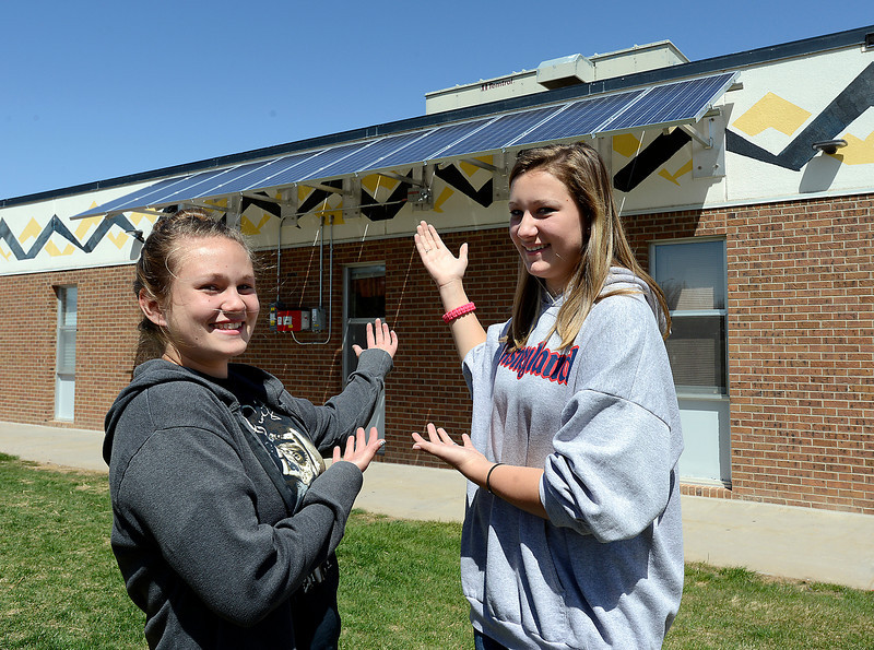Walt Clark Middle School students Sydney Spanjer, 13, left, and Kaitlynn Jennings, 13, show off the solar panels outside their school in Loveland on Friday, April 26, 2013. Both girls are Green Team members and Jennings came up with the idea to install the panels.