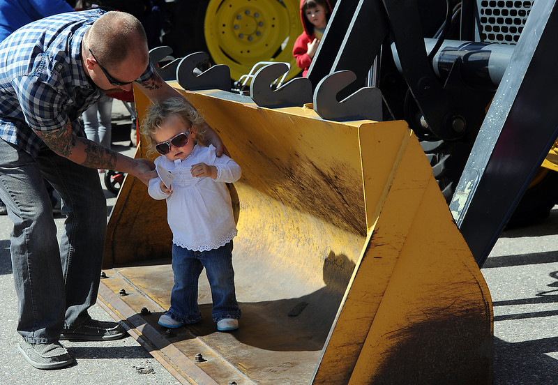 John Sweeney helps his daughter Harper Sweeney, 20 months, stand in the bucket of a front end loader during Children's Day in Loveland on Wednesday, April 24, 2013.
