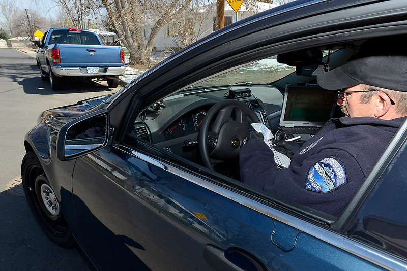 Sitting in his unmarked police car, Loveland Police officer Chuck Hoffcamp writes a citation during a traffic stop on Prospect Drive in west Loveland on Wednesday, April 10, 2013.