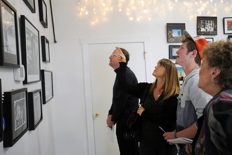 """Loveland High School senior Bailey Entner, 17, second from right, looks at photographs on display with his grandmother Sandy Reynolds, right, mother Jennifer Entner and Rep. Jared Polis, back during the 2nd Congressional District Art Show on Saturday, April 20, 2013 at the Wildfire Community Arts Center in Berthoud. Bailey's entry """"Look at Me,"""" at bottom left, was awarded second runner up in the Best Photography division."""