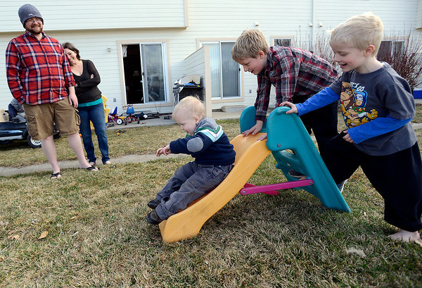 Joel Green, 4, goes down the slide after getting some help climbing the stairs by  his brothers, Caleb, 7, left, and Isaac, 5, as his parents, Ryan and Amy watch Thursday in Loveland.