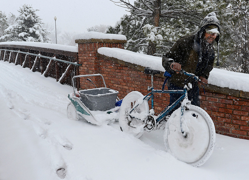 Dan Woelfle pushes his snow covered bike and trailer through the snow at the Benson Sculpture Garden Park in Loveland on Monday, April 15, 2013.