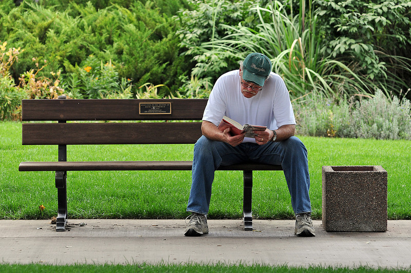 Frank Kros of Loveland takes a moment to read in near Foote Lagoon after arriving to a closed Loveland Public Library on Sunday. The library resumes Sunday hours in September.