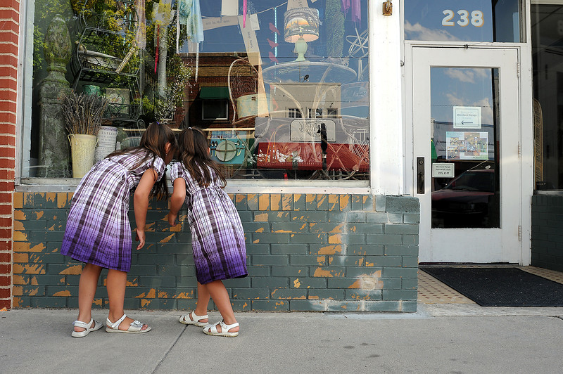 Nicole Stepina, 5, right, and her sister Nicole, 6, peer into the window at Merchant Voyage on Fourth Street in downtown Loveland on Sunday. The two were hanging out at their great-grandmother, Mary Aguilar's restaurant, Carl's Canteen.