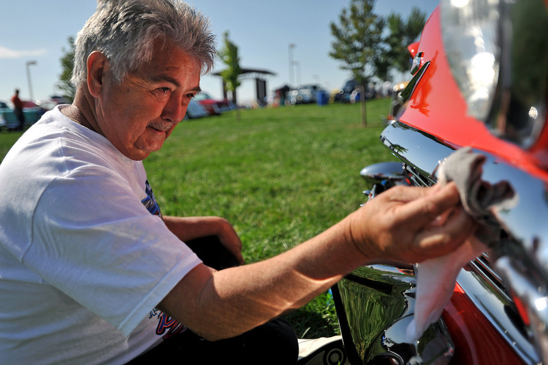 "Ken Jones of Casper Wyoming works hard to polish the chrome on the front of his wife's 1956 Chevrolet Bel Air on Sunday at the Road Knights car show at The Ranch. Jones says that he and his wife, Garnette Jones, travel all over to different car shows and has enjoyed Loveland's show saying there are ""a lot of nice cars and a lot of nice people"" at the Road Knights show this year."
