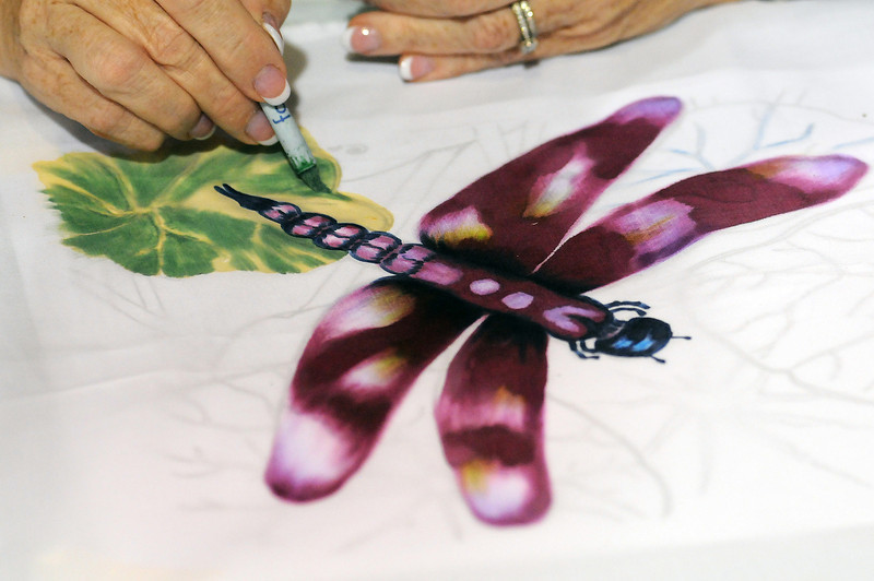 Patt Blair of Mount Baldy, Calif., uses Japanese inks to paint a dragonfly during a demonstration at the Jukebox Quilts booth on Sunday at the Rocky Mountain Quilt Festival at The Ranch.