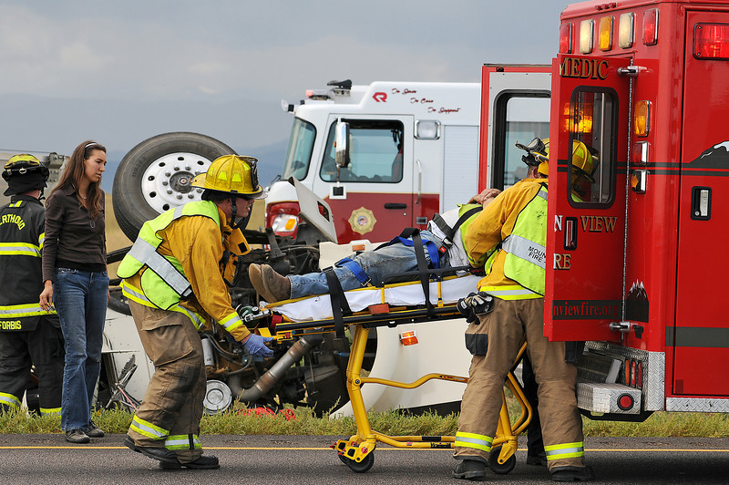 Sarah Altgelt of Boulder, left, watches as Mountain View Fire crews load the driver of a tractor trailer into an ambulance on Wednesday at mile post 248 along Interstate 25. Altgelt was one of the first people on scene and helped the driver remain calm and provided the knife that he used to cut himself free. A gold SUV cut the tractor trailer off and forced it into the median where it jackknifed and the cab rolled according to Colorado State Patrol.