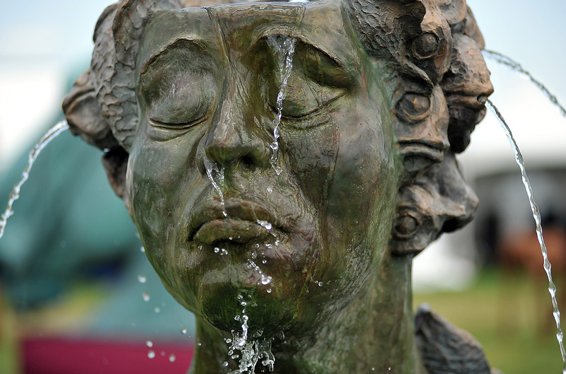 An untitled sculpture by Giuseppe Palumbo leaks water out of purposeful holes in its head Sunday at the Loveland Sculpture Invitational. The event drew many artists with a vastly differing array of pieces scattered throughout Lake Loveland and the Benson Sculpture Garden.