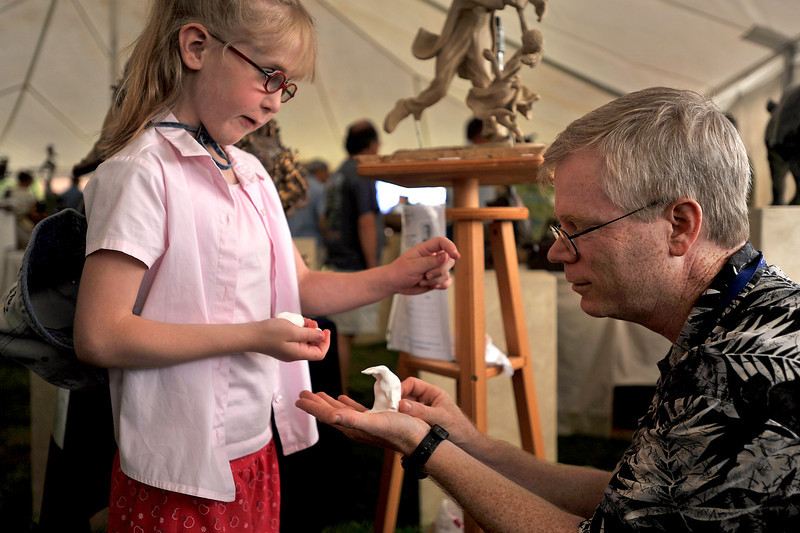 "Dakota Wiechman, 8, discusses her newly created penguin with sculptor Tim King Sunday at the Loveland Sculpture Invitational at Lake Loveland. King, who knows Wiechman from their church in Longmont, helped in the penguin-making process commenting on Wiechman's passion for the art form, ""she's definitely an up-and-coming sculptor."""