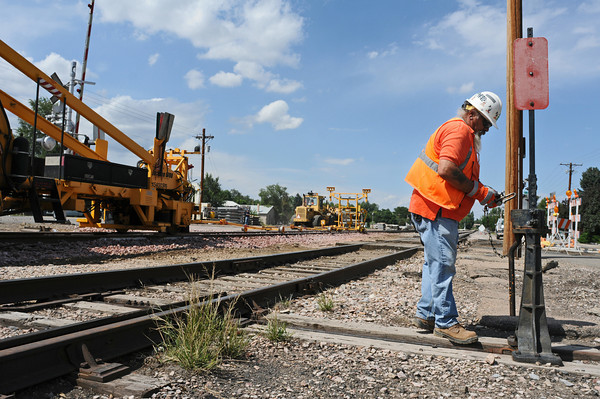 BNSF Foreman Flagman Butch Borago of Loveland switches a signal at the railroad crossing at Seventh Street on Monday. Crews will remove the old wood crossings and replace it with new concrete ones.