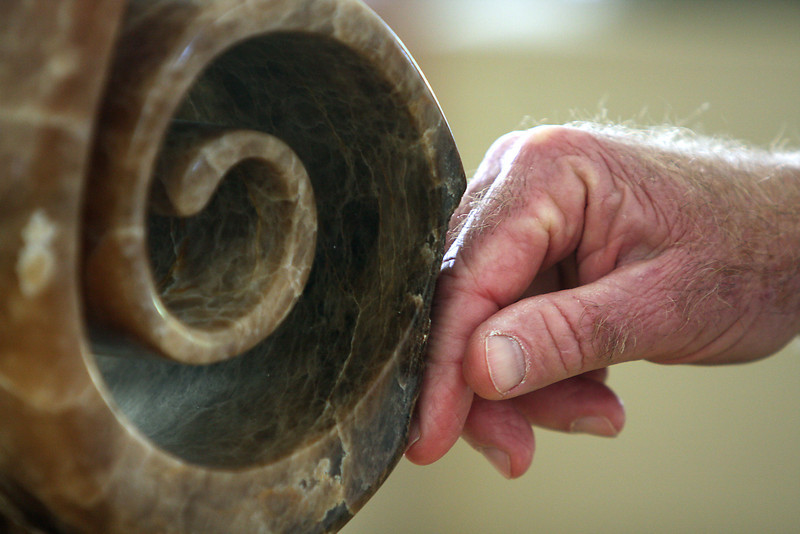 "Sculptor, Merlin Cohen, touches one of his works called ""Story of Life,"" carved out of Italian alabaster."