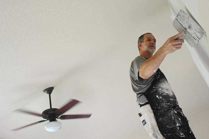 Mark Howard, owner of Advent Home Improvement smoothes on a coat of joint compound to even out a seam in a wall on Thursday at a home in Fort Collins.