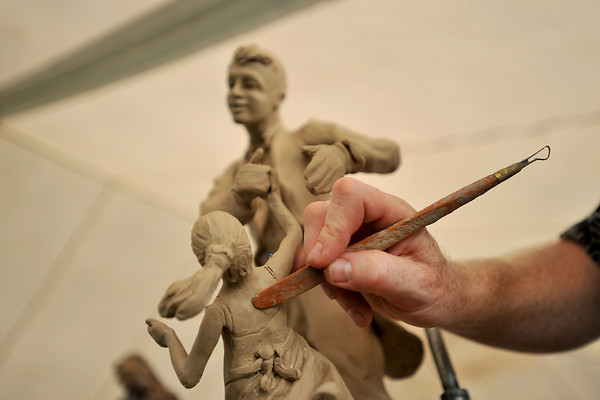 "Tim King of Longmont works on the shoulder blades of the young girl in one of his recent clay sculptures Sunday during the Loveland Sculpture Invitational at Lake Loveland. King, who is an eight year participant, says, ""I enjoy being able to create something that people can identify with."""