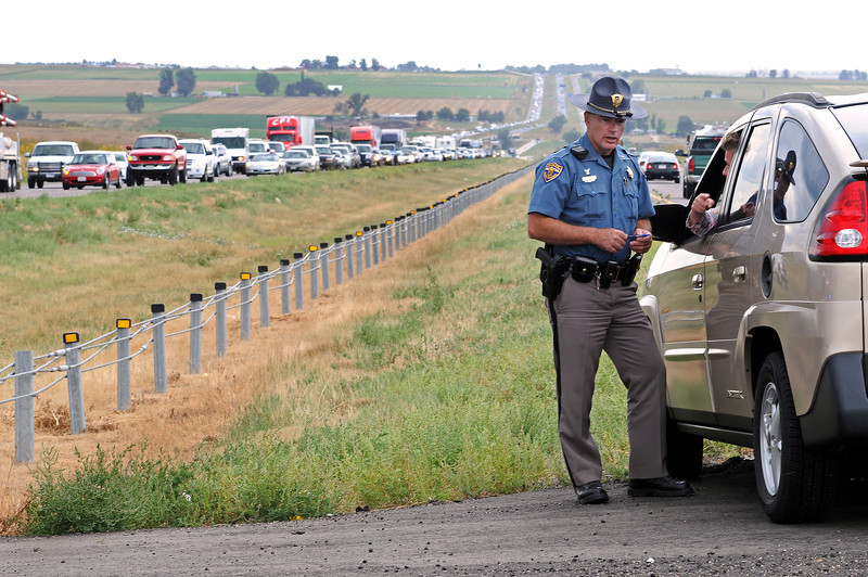 Colorado State Patrol Trooper Brian McNulty talks with the driver of a vehicle that was brought back to the scene of an accident on Wednesday on Interstate 25 at mile post 248. A gold SUV cut the tractor trailer off and forced it into the median according to Colorado State Patrol. The accident backed up traffic in both directions