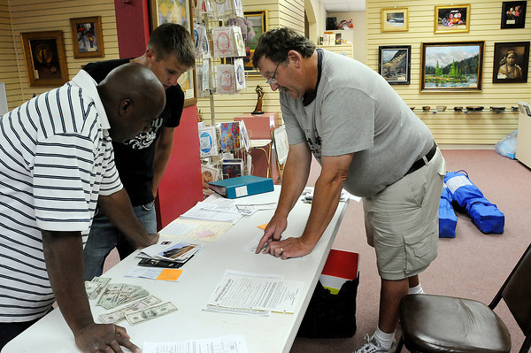 Lincoln Gallery Director Jeff Brooks, right, talks with Sean Johnson, left, and Dan Arkulary of Maui Wowi smoothies on Wednesday about the location of their booth at the Thompson Valley Art League's Art in the Park.
