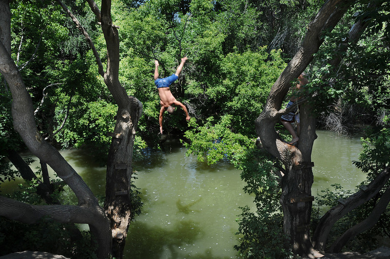 Tyler Florell, 20, of Loveland does a backflip into the Big Thompson River as his friend Cole Gladura, 15, right, waits to jump on Tuesday at the swimming hole along the Recreation Trail just south of First Street.