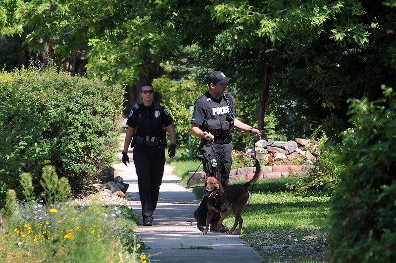 Officer Denise Martinchick K-9 Handler Steve Colburn and Kyro search the area where a suspect in the armed robbery of St. Louis Liquors was last seen near the intersection of East Second Street and Saint Louis Avenue on Tuesday. The robbery happened around 2:20 p.m., and the suspect fled on foot to the northwest of the liquor store but was not caught.