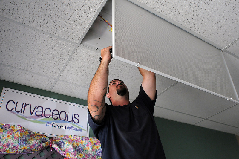 Tyler Cathey of Powerpro Electric installs a new ballast into a flourescent light fixture on Tuesday at Curves in the Orchard Shopping Center. Energy Efficient Systems inc. subcontracted Cathey, his father Dan and uncle Randall's family business to install the new lighting components that should save the women's workout location an estimated $284 per year. The Platte Valley River Power Authority is offering rebates for those companies that chose to switch to the energy efficient system.