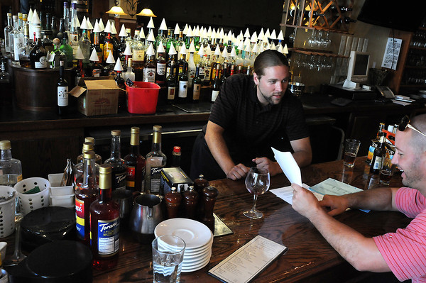 Pourhouse Managing Partner Joe Beaman, left, talks with Jamey Hancock of Republic National Distributing about the new restaurant's alcohol selection on Wednesday. The restaurant will open on Aug. 18, in the former location of Cipoletti's Italian restaurant on Fourth Street in downtown. The owners will retain most of the staff but will offer more draught beers from smaller local microbreweries and a menu with seafood and burgers.