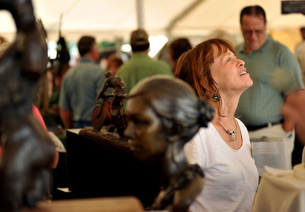 Susan Rae Westover admires the artwork of Matt Lewis Sunday at the Loveland Sculpture Invitational at Lake Loveland. The event attracted hundreds from across the country as thousands of pieces of artwork were show-cased over a three day span.