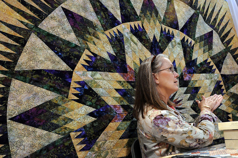 Laura Shotwell of the Fig Leaf, a quilting store in Fort Collins, talks with visitors to her booth about the quilt seen behind her on Sunday at the Rocky Mountain Quilt Festival at The Ranch. The quilt, which is an Amazon star pattern by Judy Niemeyer, took her about 10 hours to cut out and nearly 100 hours to finish.