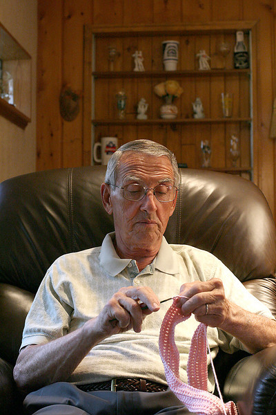 Loveland resident and cancer suvivor, Ron Mutka, crochets a pink scarf for women fighting breast cancer on Thursday at his home in Loveland. Mutka has been making these scarves and giving them anonymously to McKee Medical Center to be given out to women cancer patients.