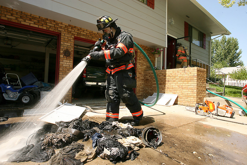 Loveland Fire and Rescue firefighter, Russell Klassen, from Station 5 sprays down oily clothing that had caught fire by spontaneous ignition Monday at 2241 Arikaree Court in Loveland.