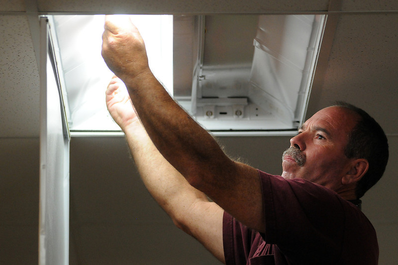 Dan Cathey of Powerpro Electric installs a new energy efficient bulb on Tuesday at Curves in the Orchard Shopping Center.