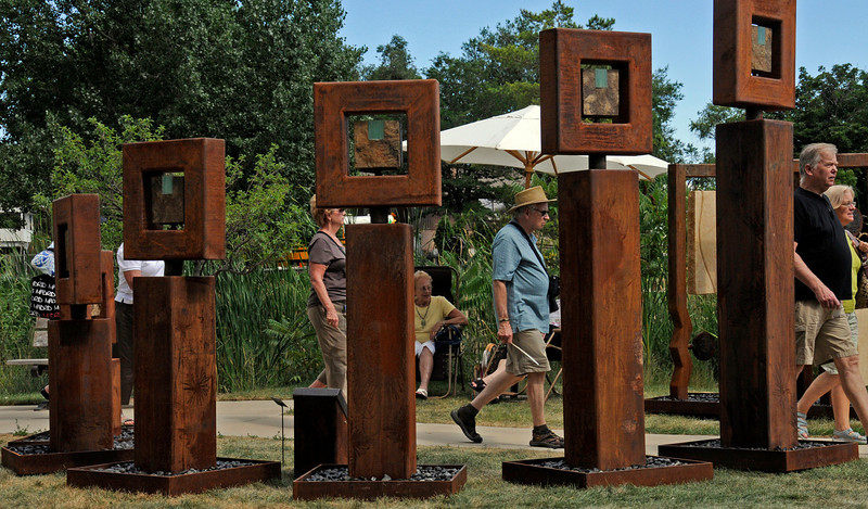 "Visitors to Sculpture in the Park walk past the sculpture entitled ""Unity"" by Brian Schader on Sunday at Benson Park Sculpture Garden."