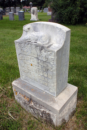 """The gravestone for Gladys Marie Rood at Lakeside Cemetary features a sculpted lamb on the top and an inscription beneath that reads """"Out Darling."""" She was born Sept. 5, 1909, and died just four months later. About 112 new grave sites have opened in the cemetary with the closure of access roads there."""