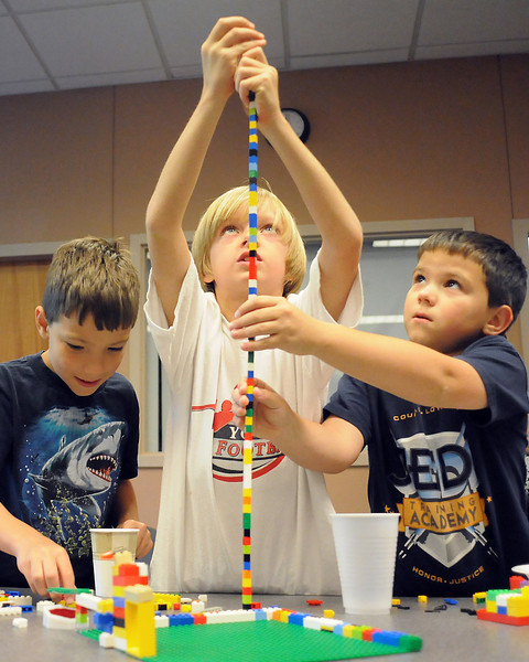 "Dominic DeMartine, 8, left, Jameson Greene, 7, and Alexander DeMartine, 8, build a skinny tower out of Lego blocks during an event at the Loveland Public Library on Saturday for fans of the toy. The boys named their creation ""Lego Skyscraper"" and  were able to stack 85 pieces together before it got too wobbly for any more."