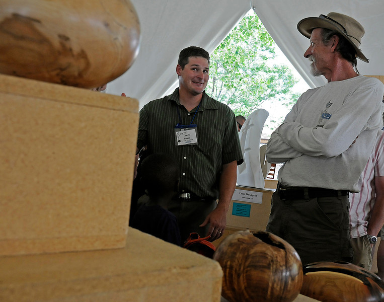 Loveland resident Travis Bauer, left, explains the art of woodturning to Ralph Klinger Sunday during Sculpture in the Park at North Lake Park in Loveland. Travis, a Civil Engineer by trade, spends most of his free time turning wood into art.